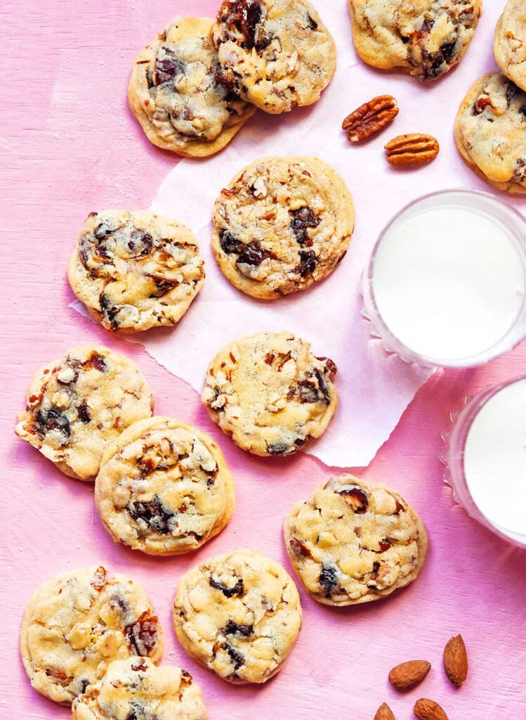 Chewy date cookies arranged in a flat layer on a pink background alongside some pecans and two glasses of milk