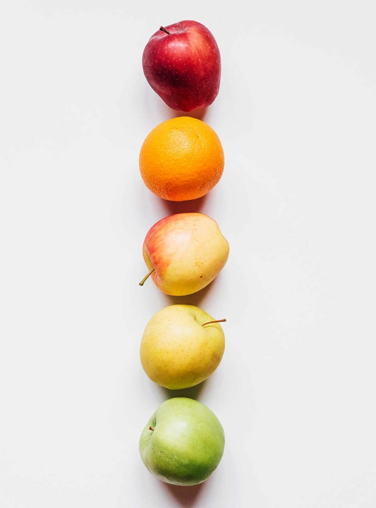 A rainbow of apples and an orange laid out in a vertical line from red to green