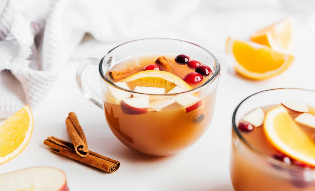 A glass of homemade apple cider garnished with cinnamon sticks, cranberries, and chopped fruit