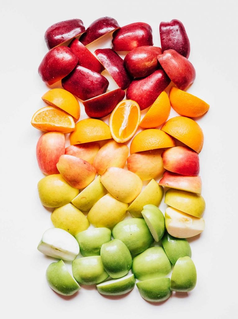 A rainbow of quartered apples and sliced oranges laid out on a white background