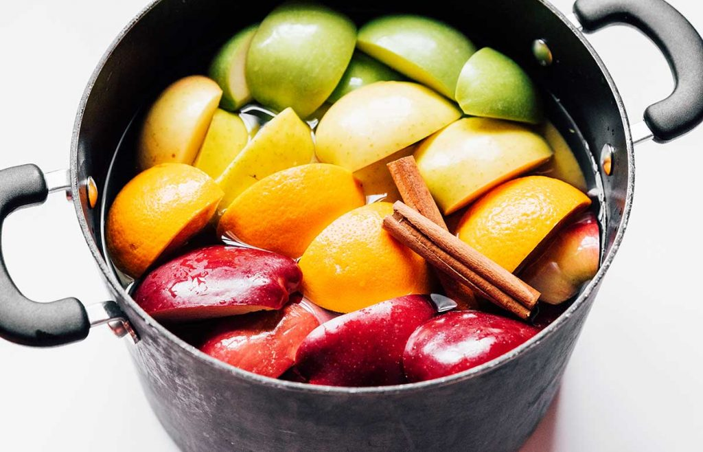 A stove pot filled with homemade apple cider ingredients like quartered apples, sliced oranges and cinnamon sticks