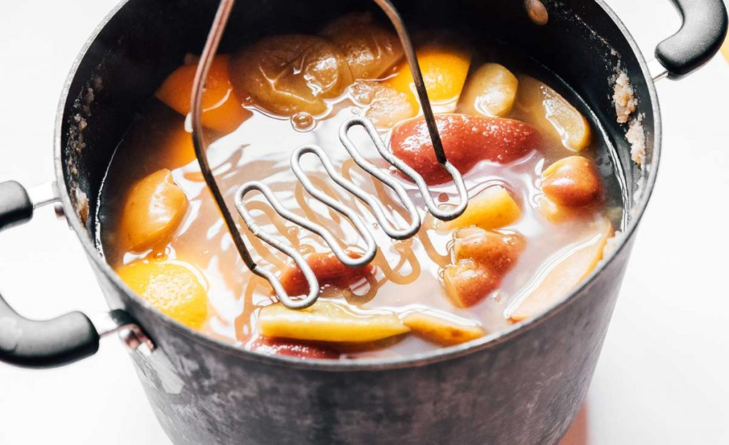 Mashing homemade apple cider ingredients in a stove pot