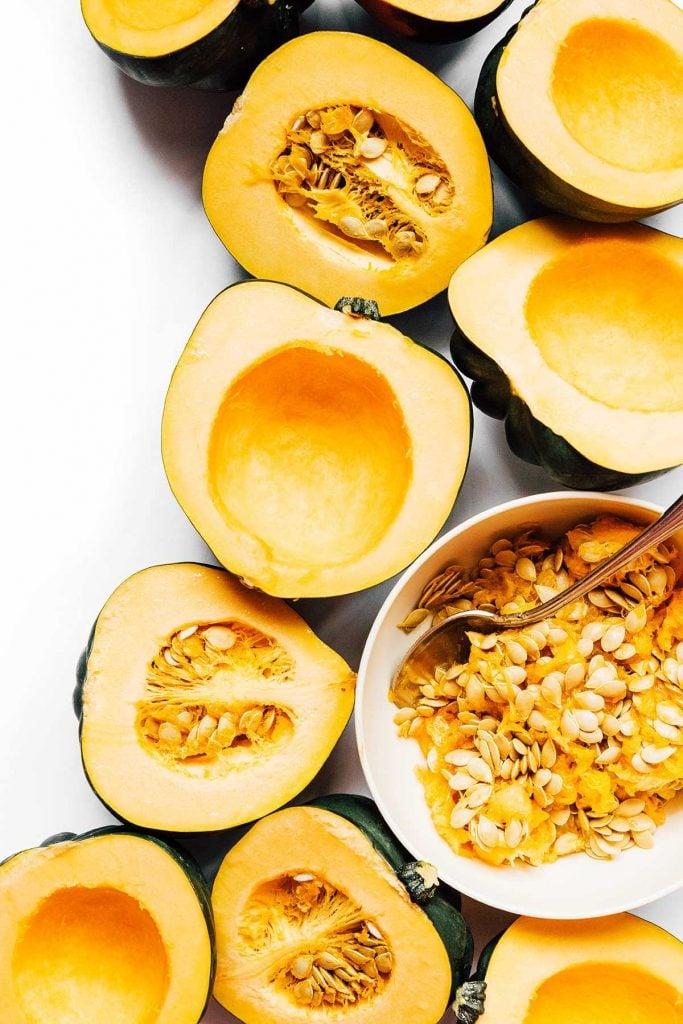 Halved acorn squash on a white background