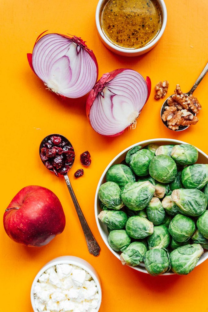 Various roasted Brussels sprout salad ingredients including vinaigrette, red onion, walnuts, Brussels sprouts, apple, and dried cranberries, measured and laid out on an orange background