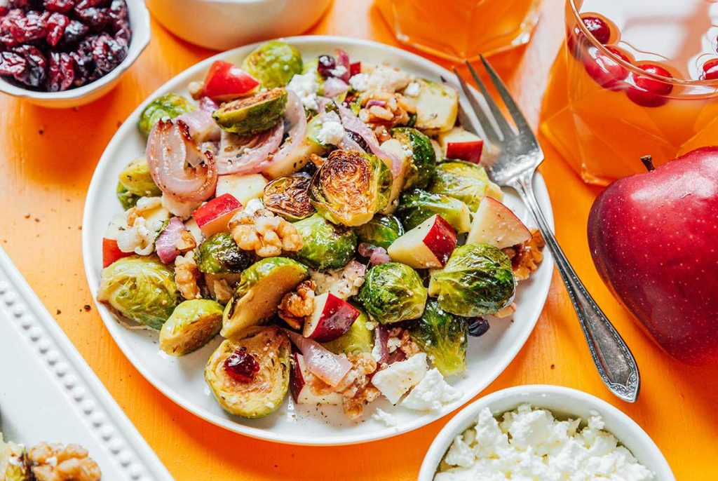 A white plate filled with roasted Brussels sprout salad