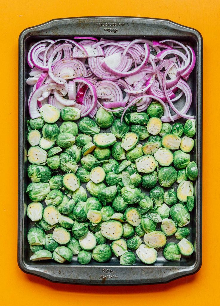 Sliced red onion and halved Brussels sprouts laid out on a baking sheet and topped with olive oil, salt, and pepper