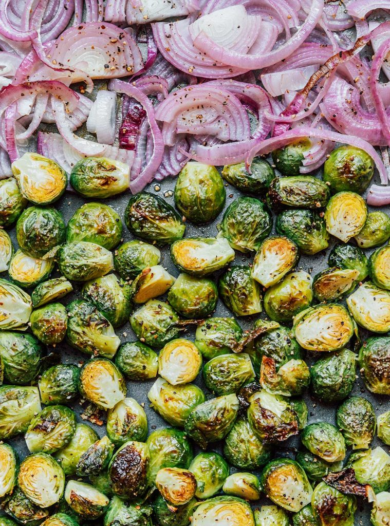 A close up view of roasted red onion slices and Brussels sprout halves
