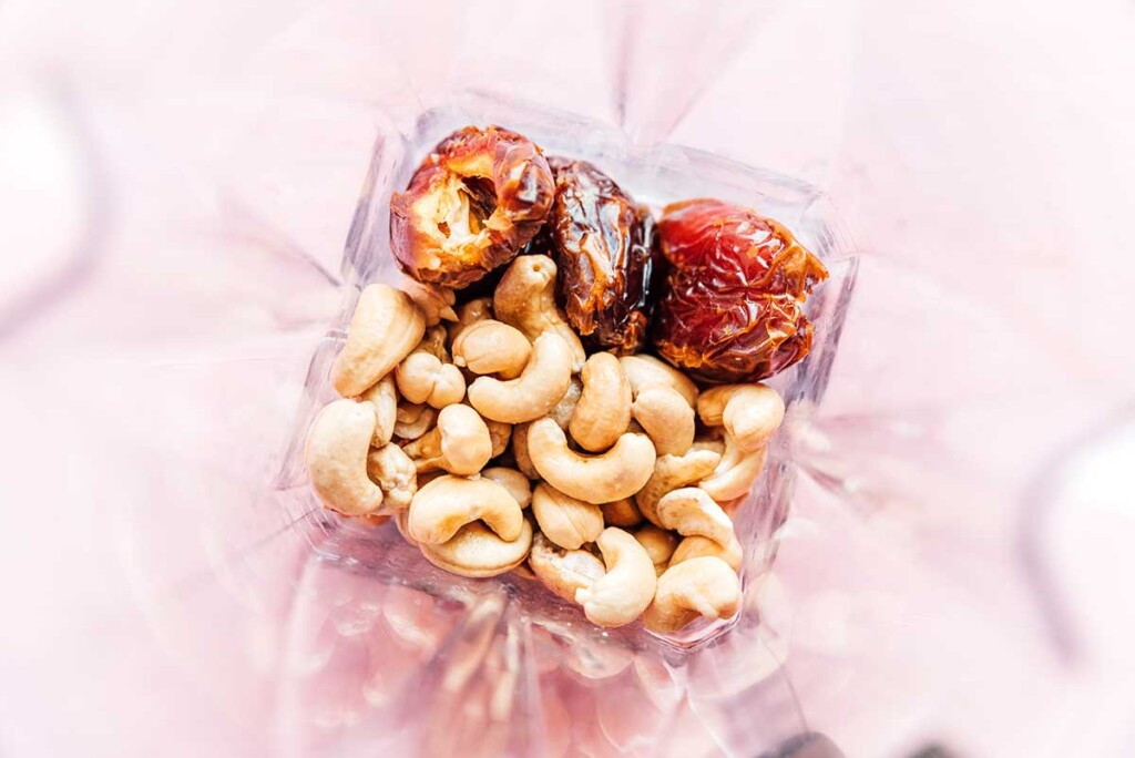 A food processor filled with cashews and pitted, halved dates