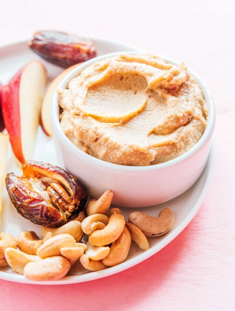 A white bowl filled with sweet cashew cream on top of a white plate surrounded by apple slices, dates, and cashews