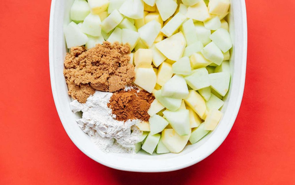 A casserole dish filled with cubed apples, brown sugar, flour, and cinnamon