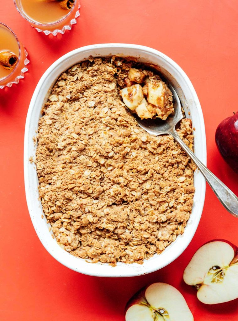 A metal spoon scooping a spoonful of vegan apple crisp from a casserole dish