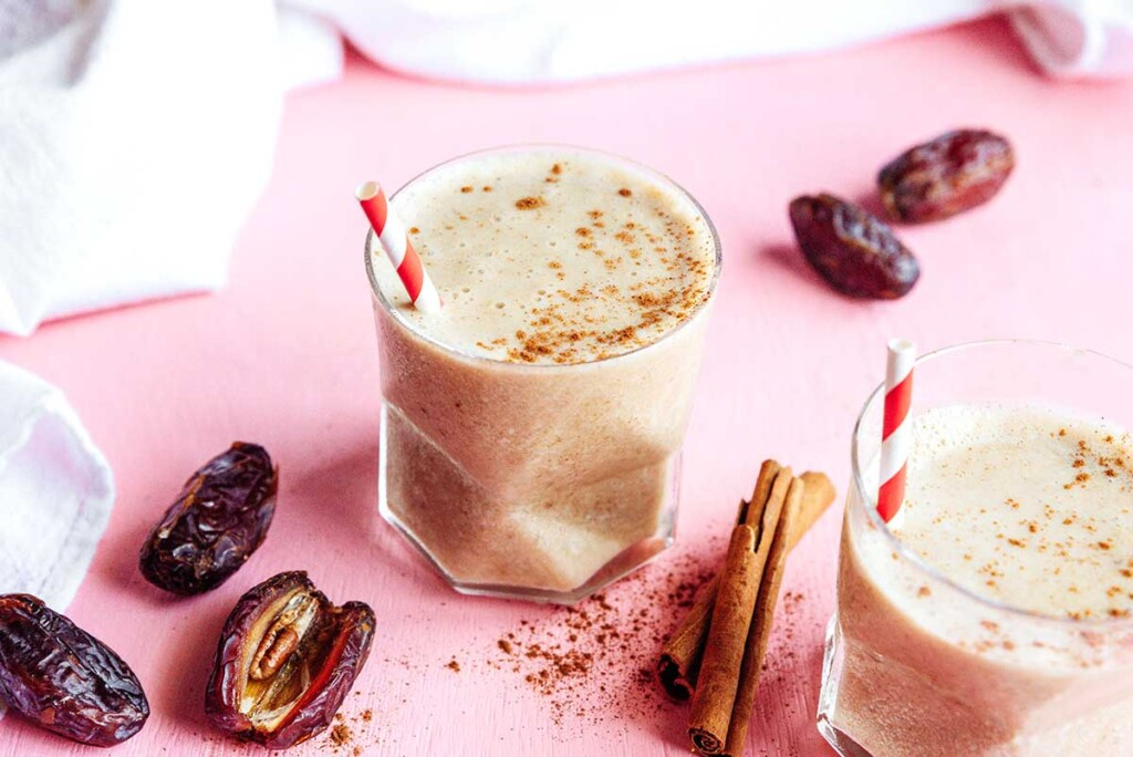 A glass filled with a healthy date shake and topped with cinnamon powder