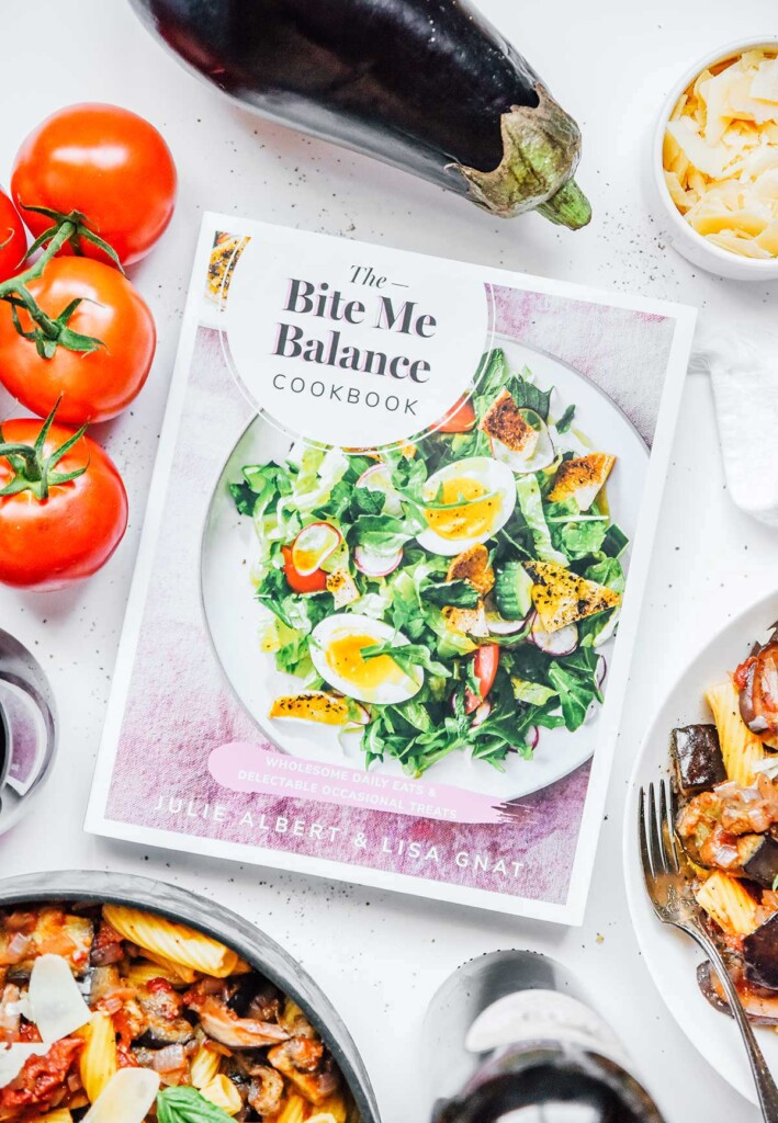 """""""The Bite Me Balance Cookbook"""" surrounded by dishes of vegetable bolognese and various ingredients"""