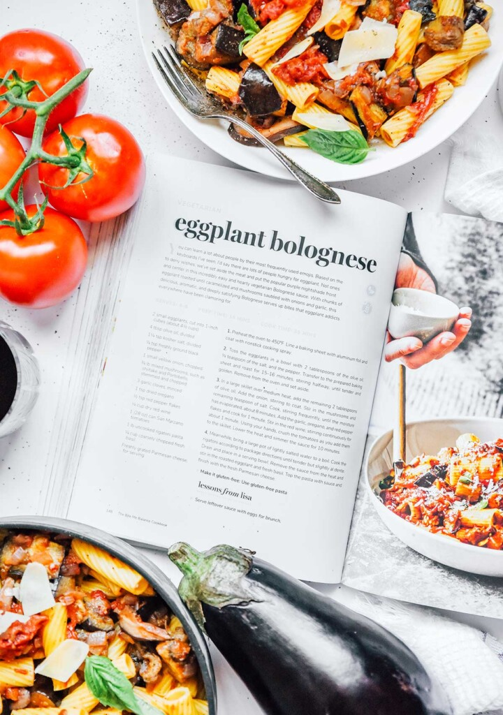 """""""The Bite Me Balance Cookbook"""" opened to the Eggplant Bolognese page, surrounded by the completed dish and a few tomatoes"""