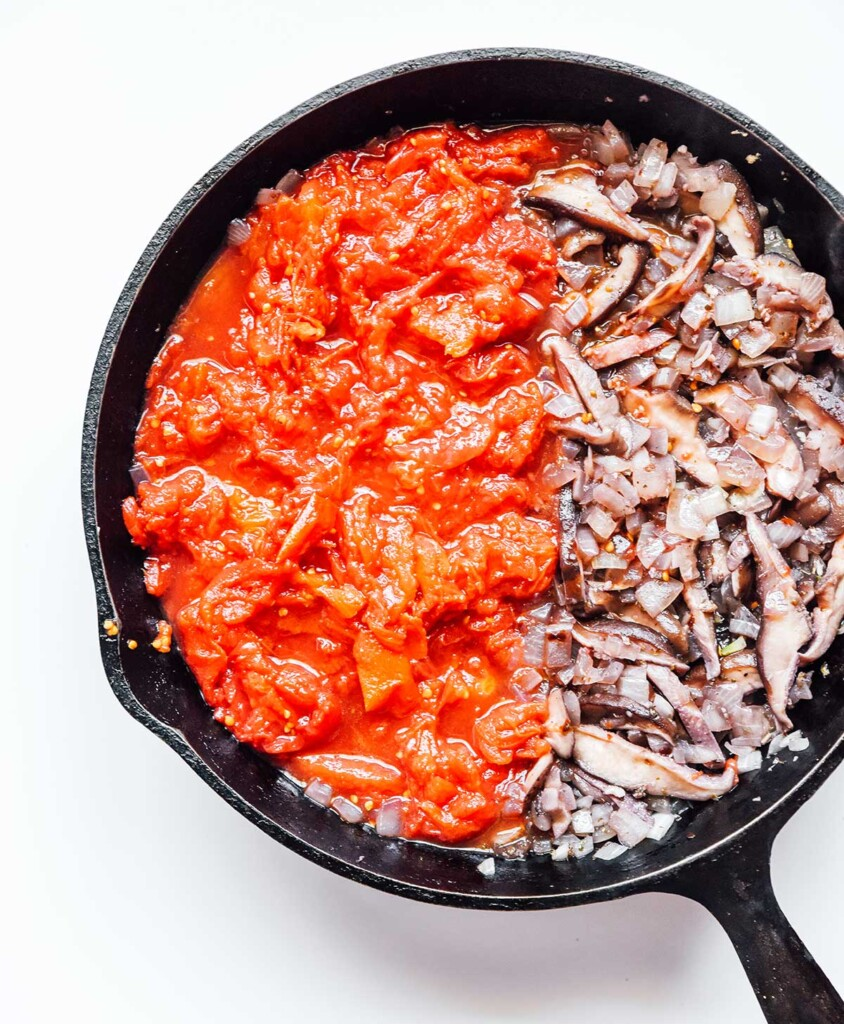 A cast iron skillet filled with sautéed mushrooms and onions and crushed tomatoes
