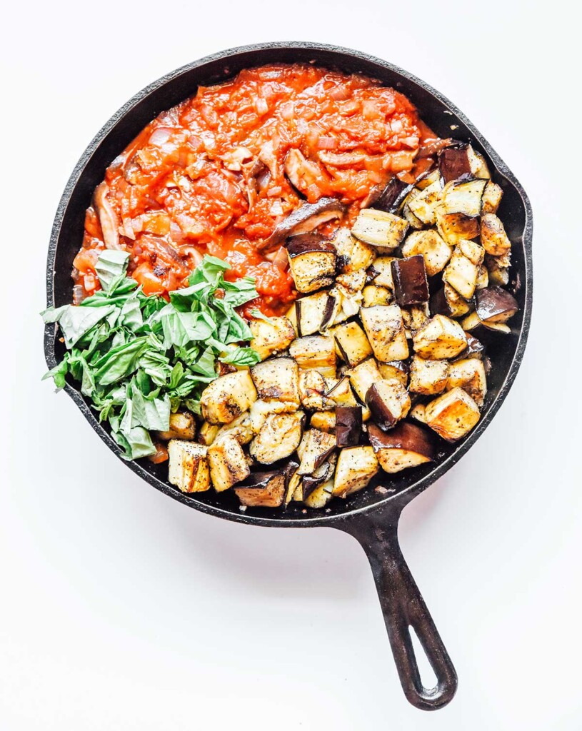 A cast iron skillet filled with vegetable bolognese sauce ingredients