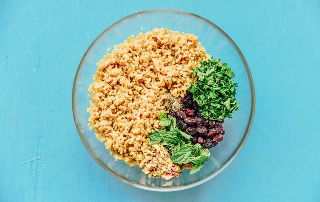 A clear glass bowl filled with cooked freekeh, parsley, mint, raisins, and seasonings