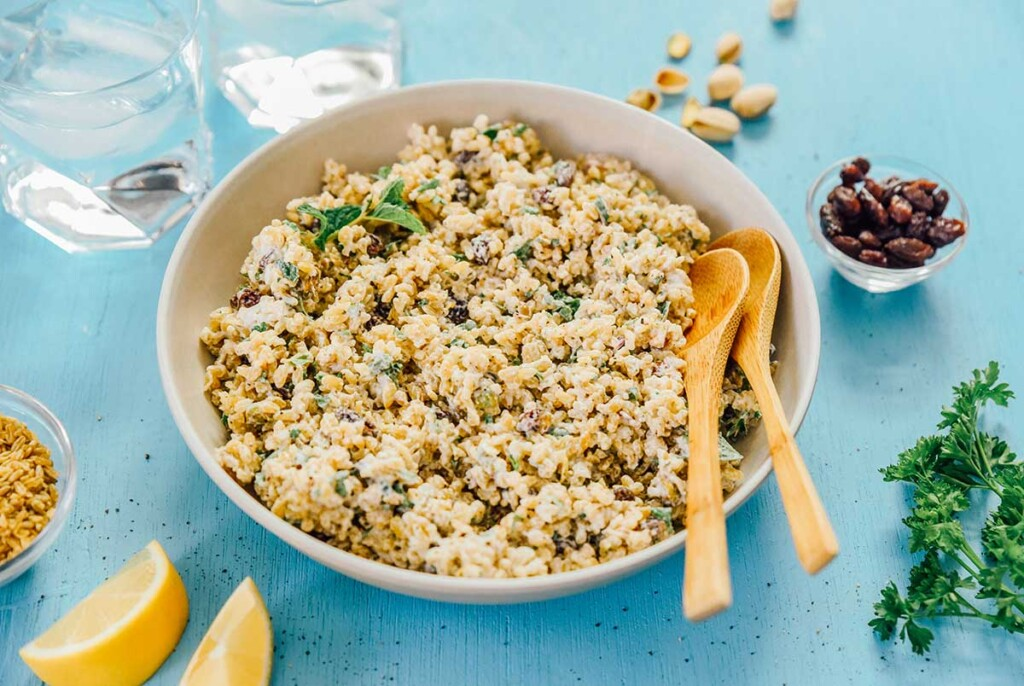 A large white serving bowl filled with freekeh salad with yogurt dressing