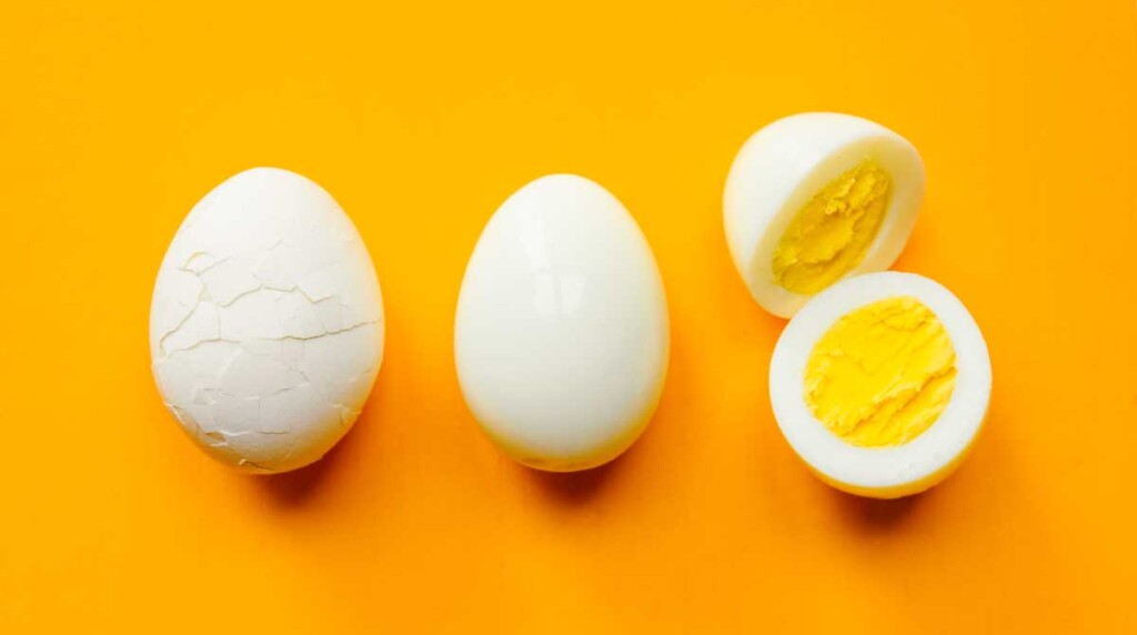 Three hard boiled eggs illustrating how to prepare the eggs: crack, peel, and cut in half