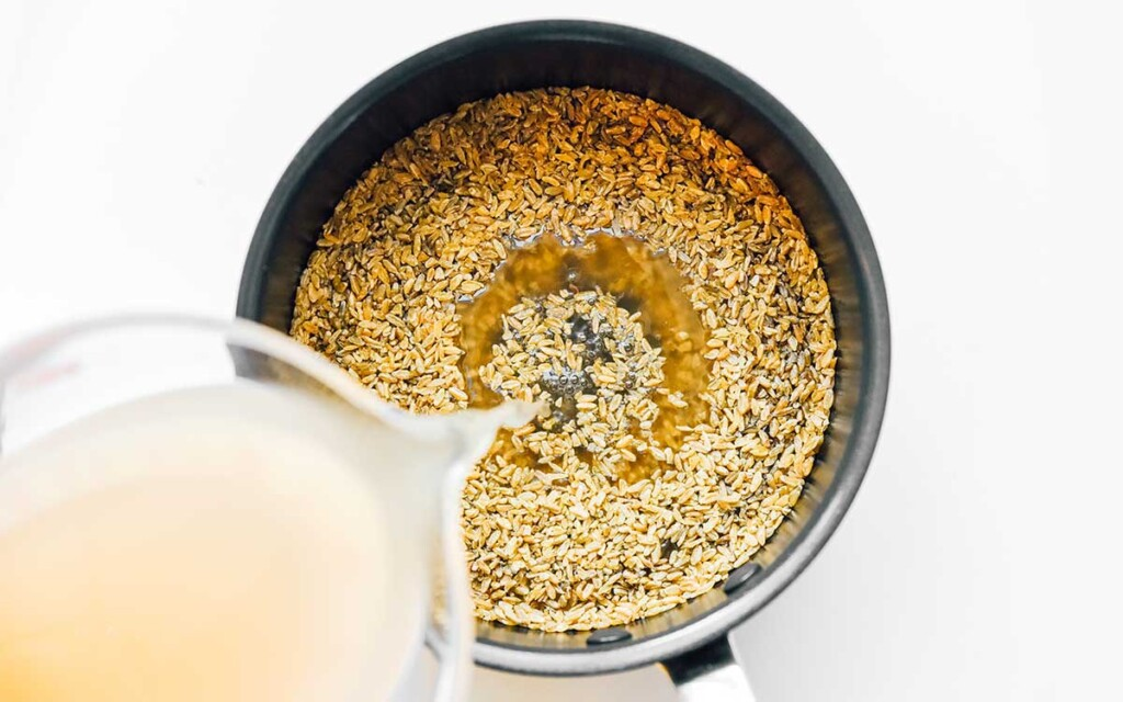 Pouring water into a sauce pot filled with uncooked freekeh