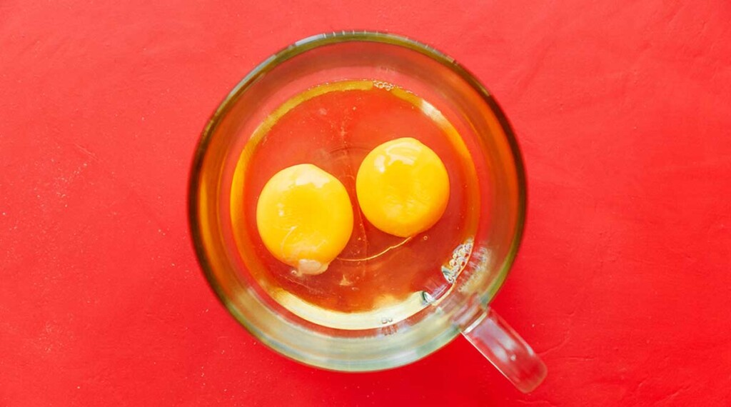 Two eggs in a clear glass mug