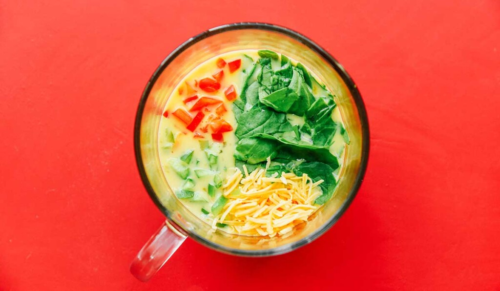 Whisked eggs and milk in a clear glass mug topped with diced red pepper, diced green pepper, chopped spinach, and shredded cheddar cheese