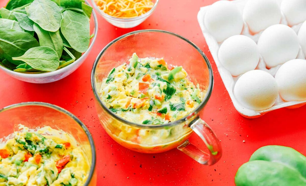 Veggie mug omelette ingredients mixed together in a clear glass mug