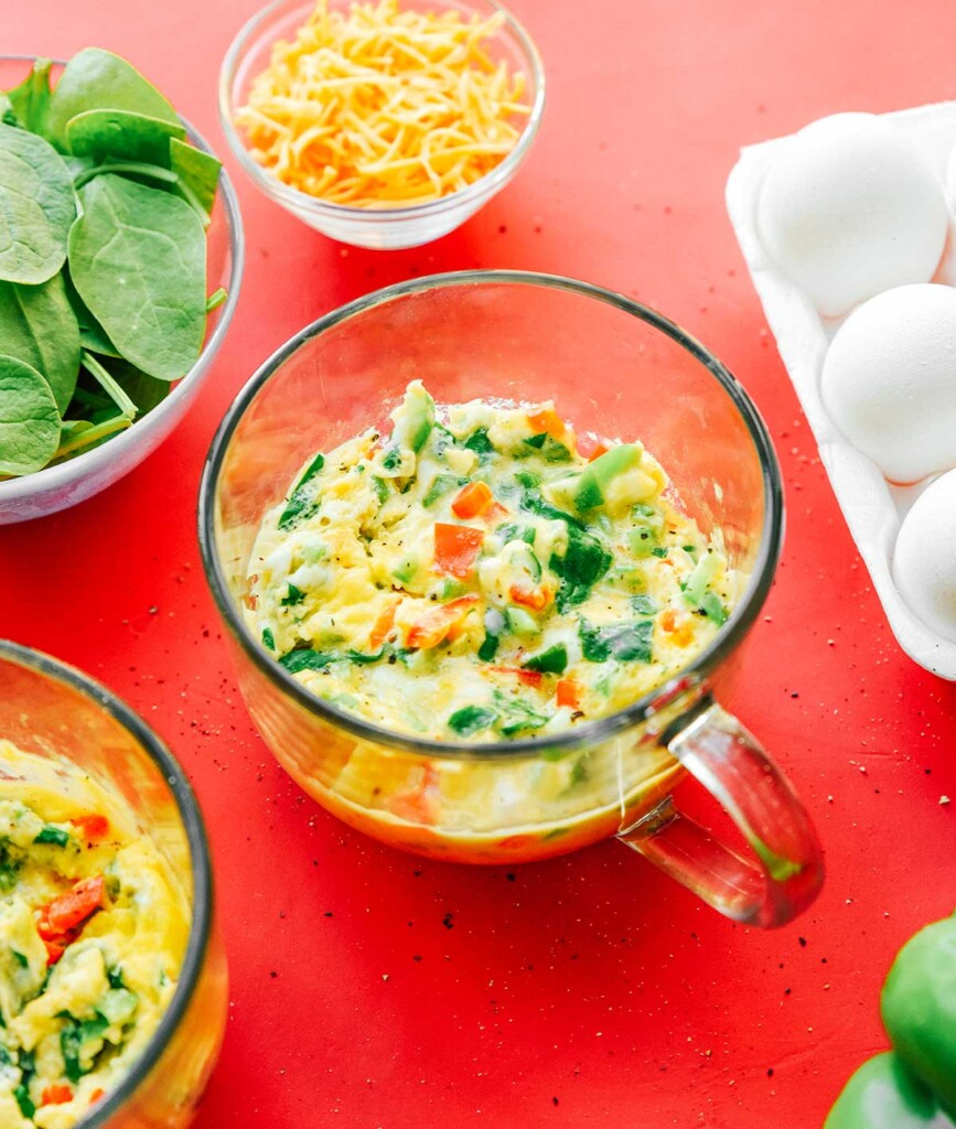 A clear glass mug filled with mixed veggie mug omelette ingredients