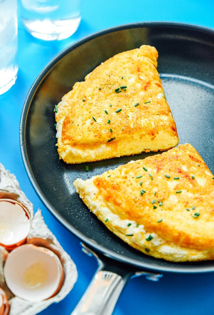 Two halves of a folded, fluffy soufflé omelette in a skillet
