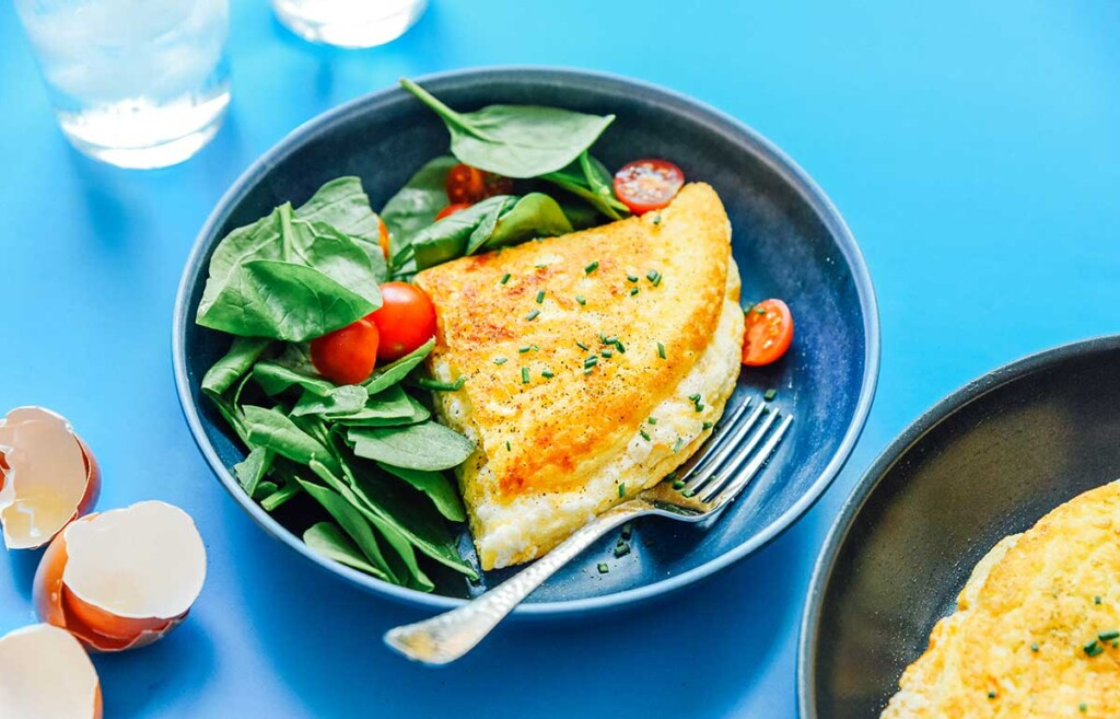 Half of a folded fluffy soufflé omelette on a plate alongside spinach and cherry tomatoes