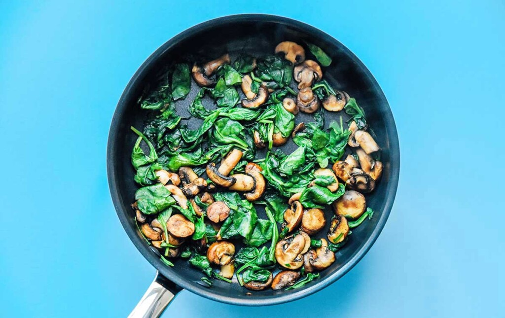 A skillet filled with sautéed mushrooms and spinach