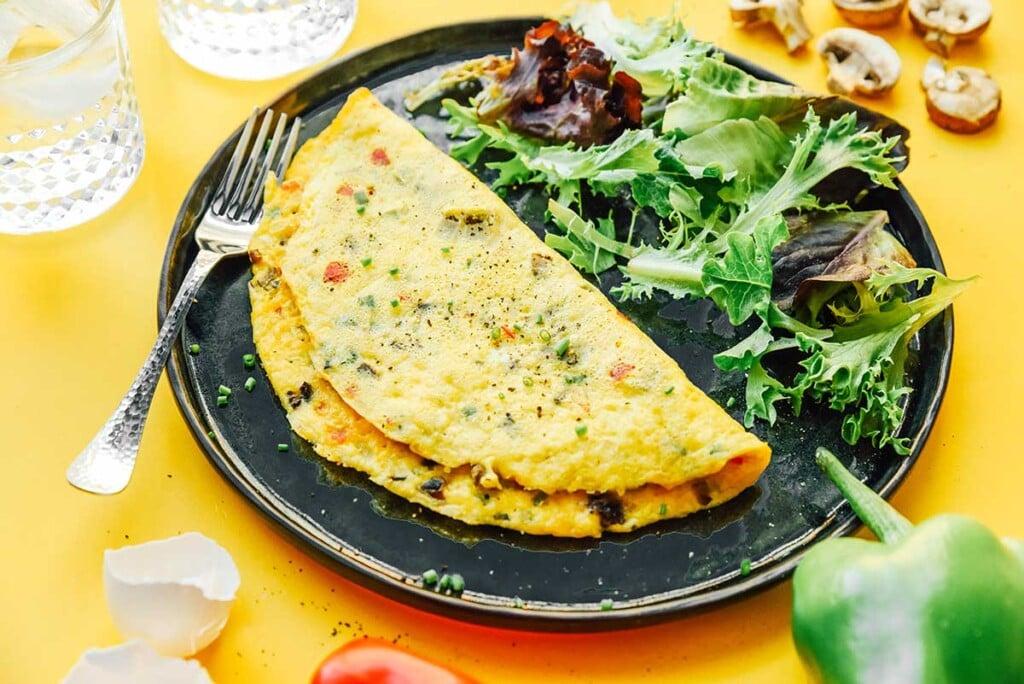 A folded veggie omelette on a plate alongside spring mix