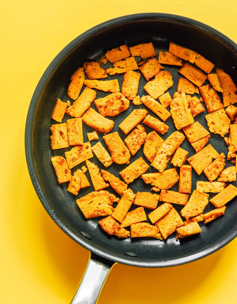 A skillet filled with an even layer of cubed, uncooked seitan