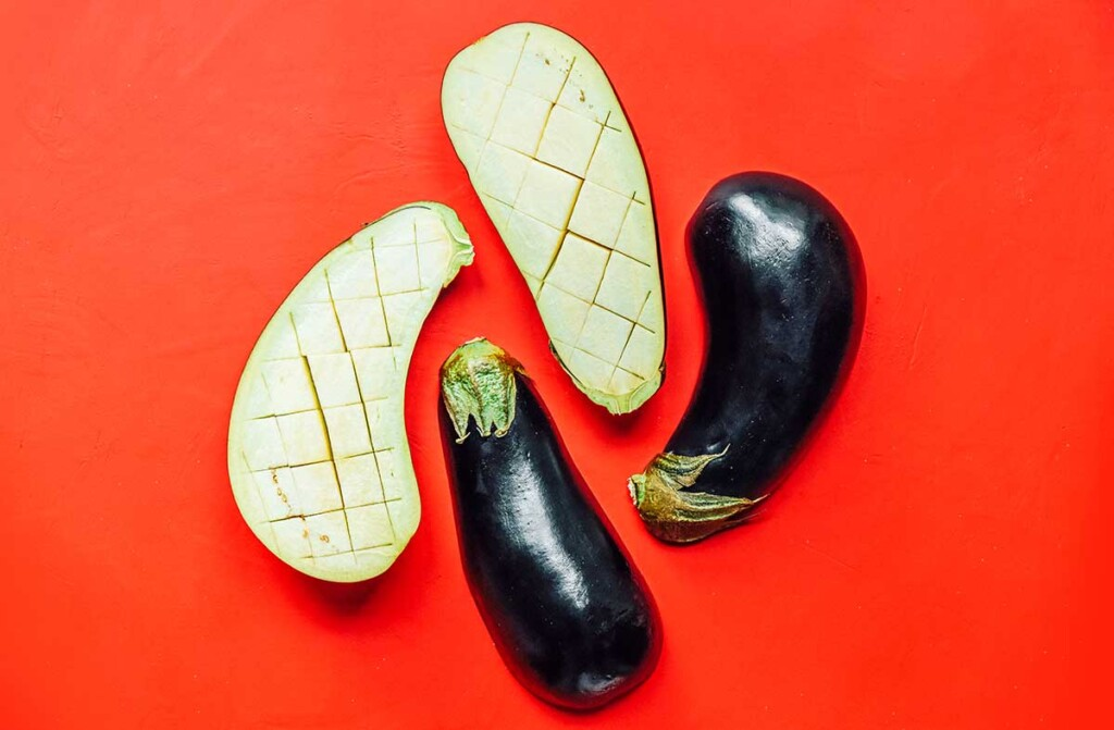 4 eggplant halves, with two facing down, and two facing up, displaying how to properly scour it
