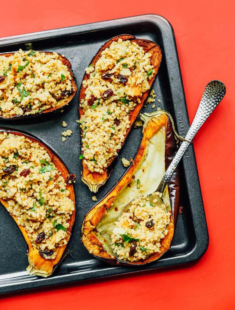 A baking sheet with three stuffed eggplants and a fourth that is begin filled with the stuffing