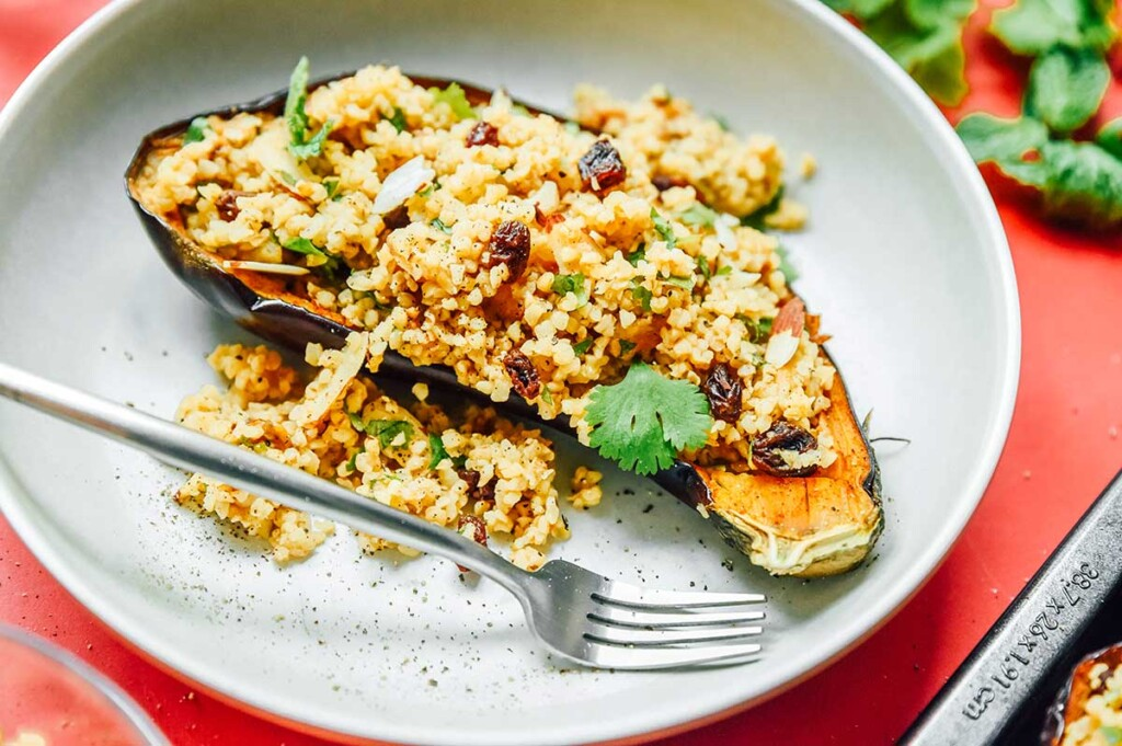 A gray plate filled with one serving of bulgur stuffed eggplant topped with Greek yogurt, salt, and pepper