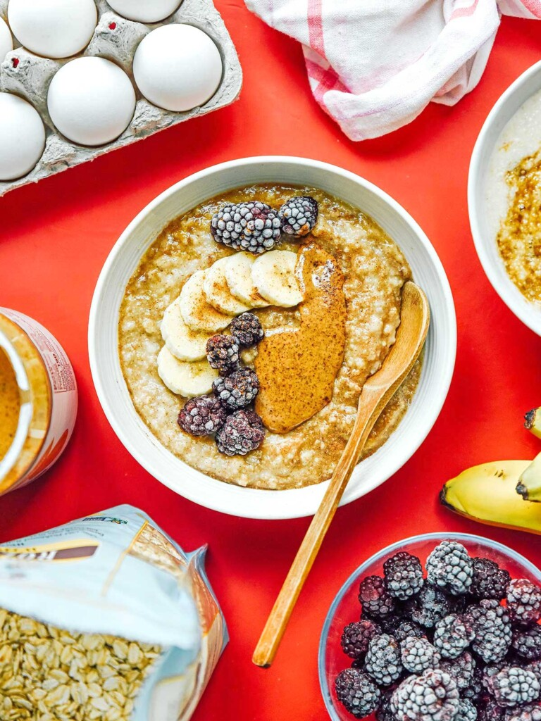 A white bowl filled with egg white oatmeal and topped with bananas, raspberries, peanut butter, and brown sugar