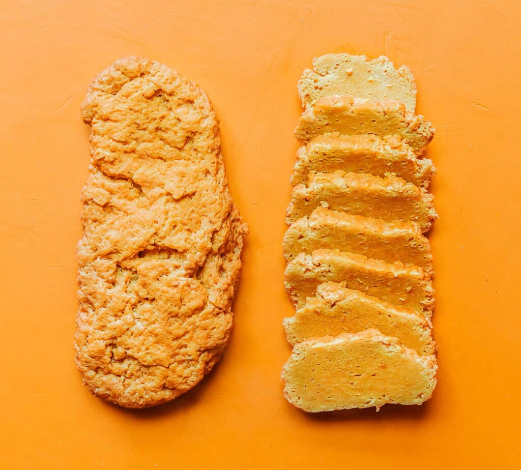 A whole and a sliced loaf of seitan sitting side by side on an orange background