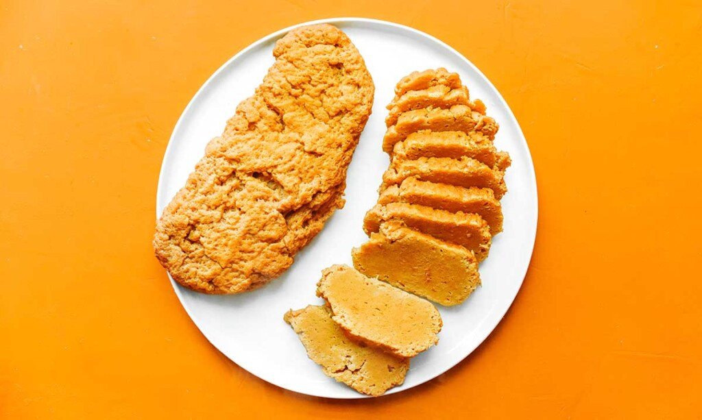 A whole and a sliced loaf of seitan sitting side by side on a white plate
