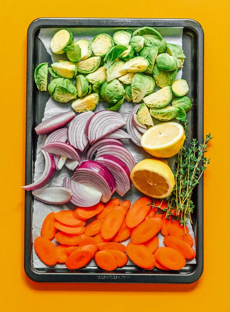 A sheet pan filled with halved Brussels sprouts, sliced red onions, sliced carrots, a halved lemon, and sprigs of thyme