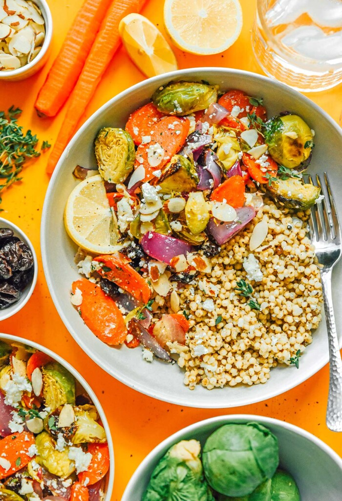 A roasted vegetable grain bowl filled with seitan, red onion, Brussels sprouts, carrots, lemon slices, feta cheese, and more
