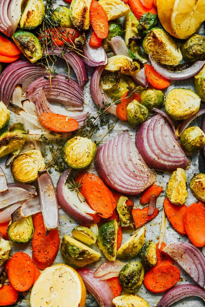 A close-up view detailing the texture of freshly roasted red onion slices, carrot slices, and halved Brussels sprouts
