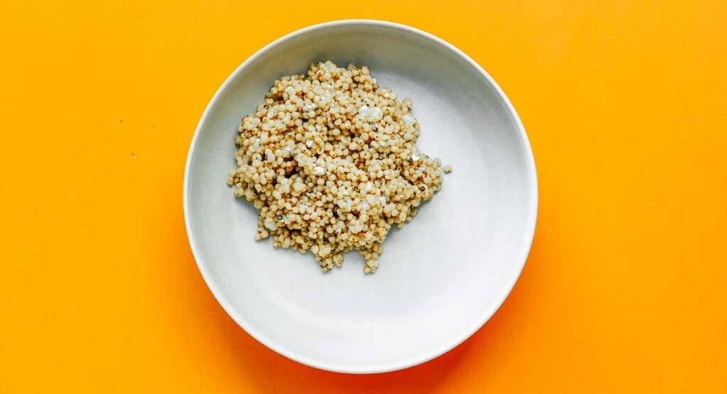 A white bowl filled with freshly cooked and fluffed sorghum