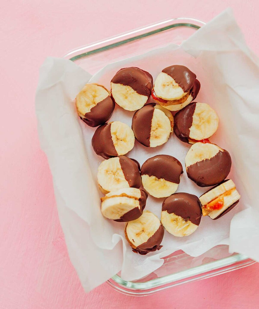 13 stuffed banana bites in a glass container lined with parchment paper
