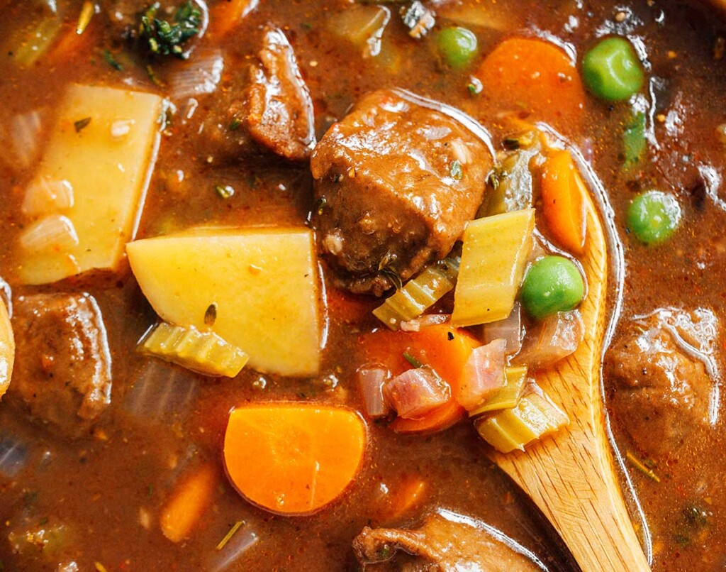 A close-up view of a wooden spoon in a bowl of vegan beef stew