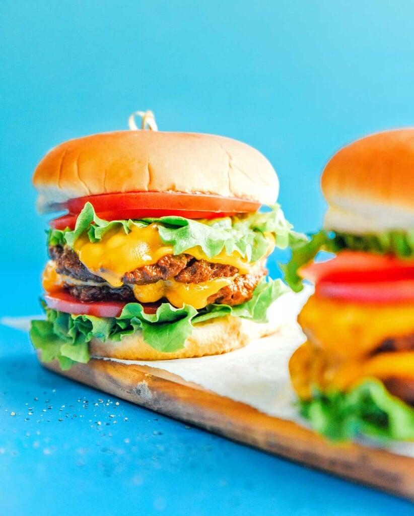 A double seitan burger on a fluffy bun with tomato, lettuce, and cheese
