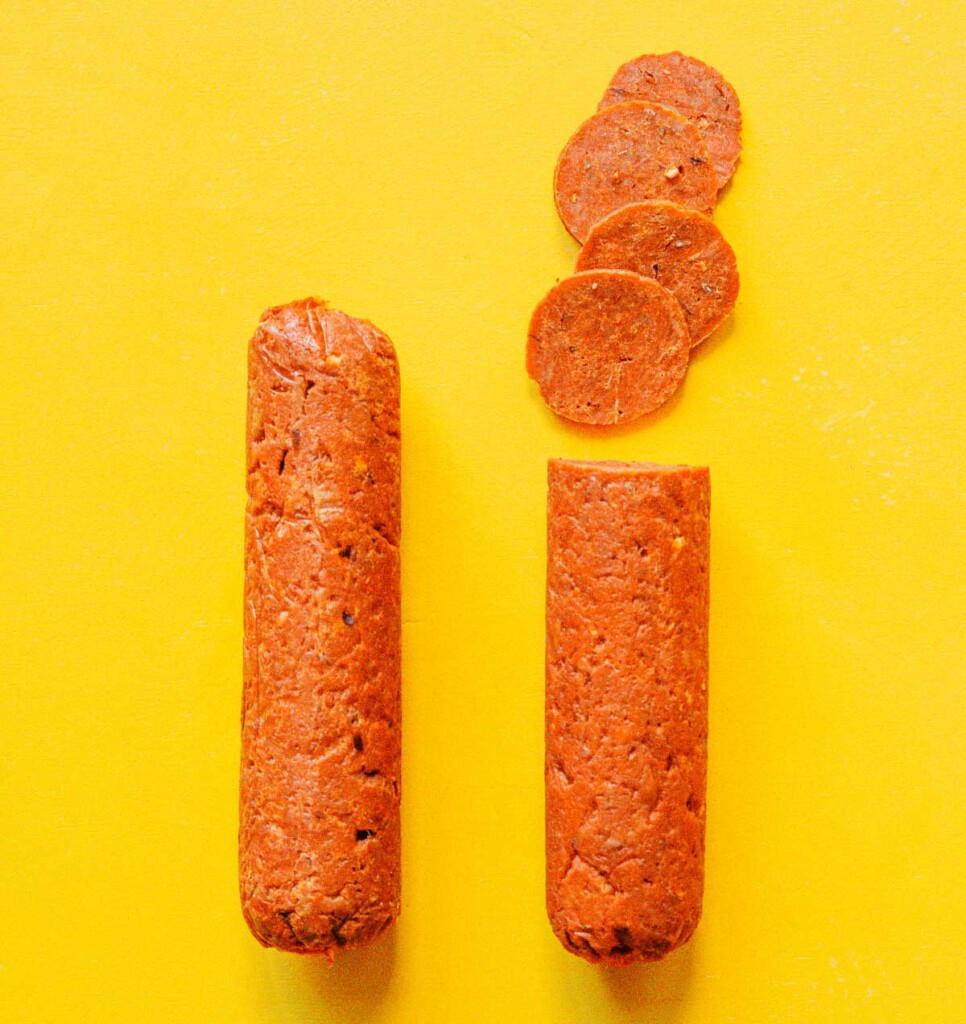Two logs of vegan pepperoni side by side on a yellow background