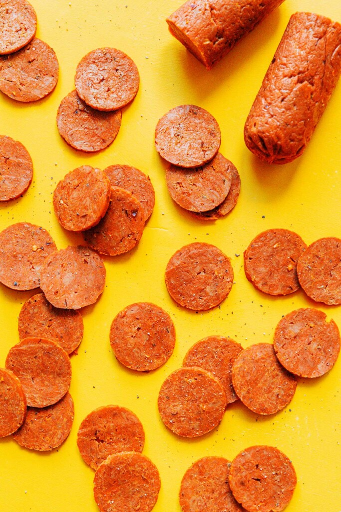 A yellow background scattered with slices of seitan pepperoni
