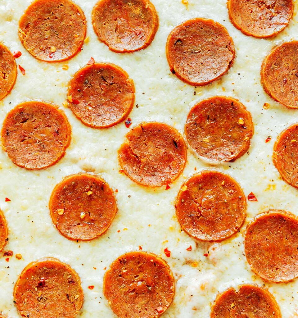 An up-close view of homemade pizza featuring cheese and vegetarian pepperoni