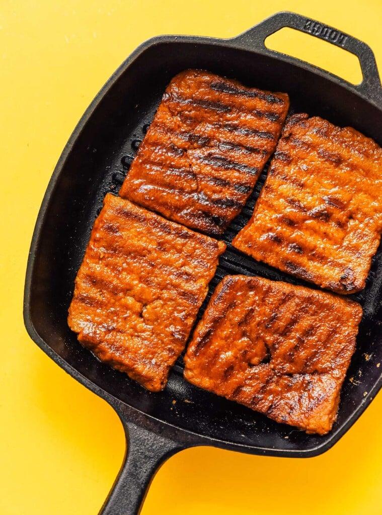 Four freshly seared seitan steaks in a cast iron skillet